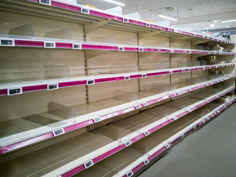 Empty shelves in supermarket store due to coronavirus covid-19 outbreak panic. Food supply shortage in Paris France
