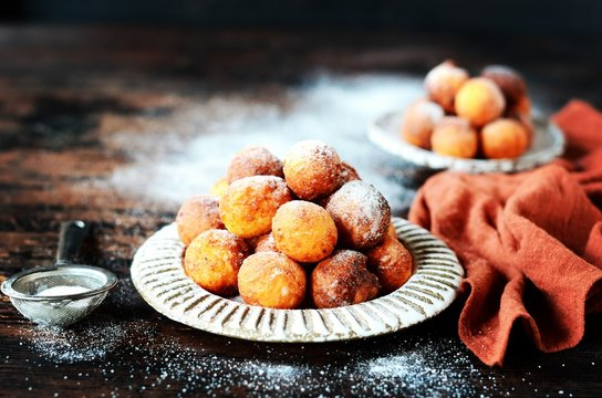 Cottage cheese donuts in a ceramic dish on a dark wooden table