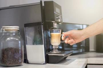 Fototapeta Latte macchiato z ekspresu. Ręka chwyta gotowy napój. obraz