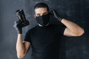 Young man Photographer in a protective black mask and gloves on a dark background holds a camera in his hands taking pictures. Concept Photo business and coronovirus.