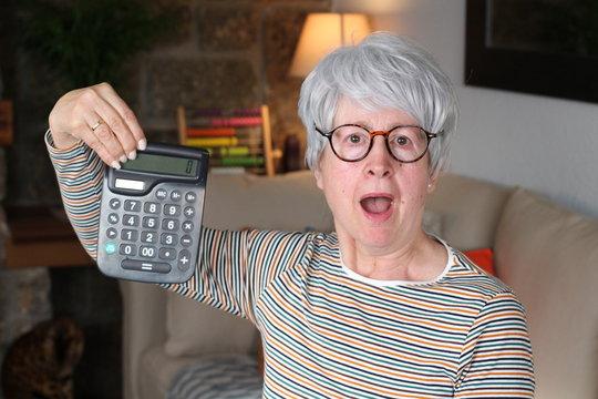 Retired senior woman holding calculator