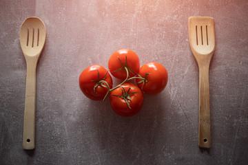 Obraz Czerwone pomidory na gałązce obok drewnianych łyżek kuchennych. - fototapety do salonu