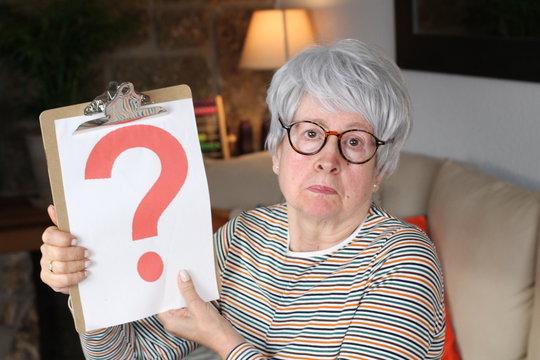 Senior lady holding question mark