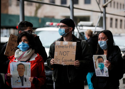 Healthcare workers at Mount Sinai Hospital hold photos of sick colleagues during a protest demanding critical Personal Protective Equipment (PPE) to handle patients during the outbreak coronavirus disease (COVID-19)  outbreak, in New York