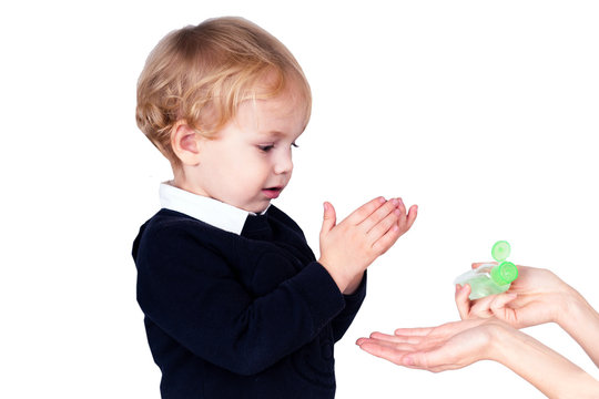 mother applying sanitary antiseptic on son's hand isolate on white background . boy wearing hygienic mask