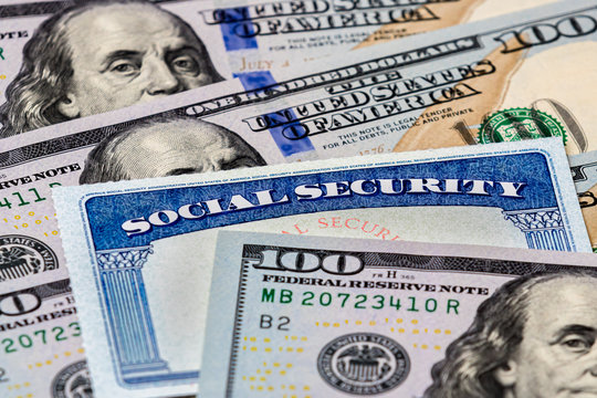 Closeup of social security benefits identification card with 100 dollar bills