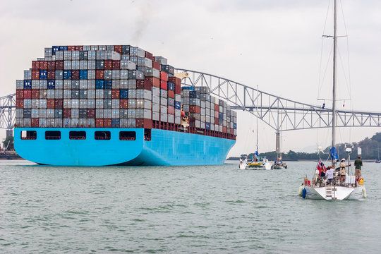 Panama City, Panama - 02-16-2020, container vessel leaving the Panama Canal and passing the bridge of the Americas, the only road connection between north and south America