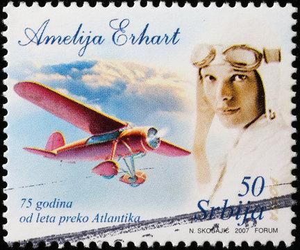 Flight across Atlantic of Amelia Earhart on postage stamp
