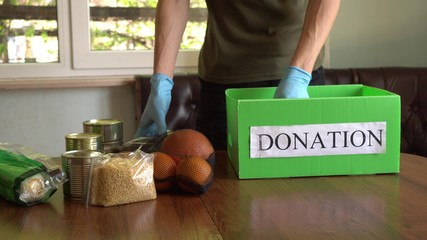 Coronavirus Relief Funds and Donations. Volunteer in the Protective Medical Mask and Gloves Putting...