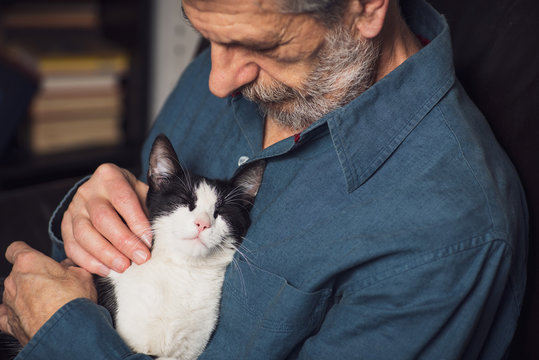 Senior man petting his cat on a sofa