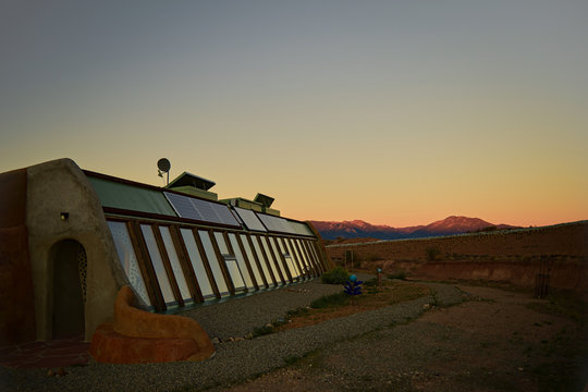 Front side view of self sustaining eco-friendly Earth ship home at sunset with mountains in background of landscape in Toas, New Mexico.