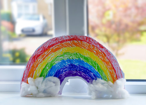 Drawing colouful rainbow with cotton wool on white paper in the window on sunny day morning. Home schooling, Stay at home Social media campaign for coronavirus prevention concept