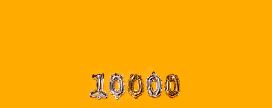 10,000 followers numbers foil balloons on yellow background. Blogger blogging followers concept, top view, flat lay.