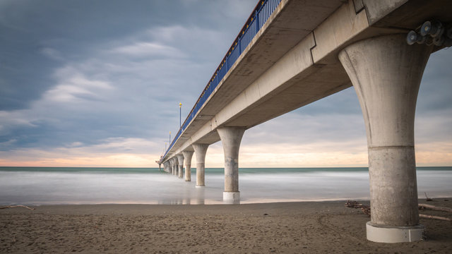 Massive concrete pier leading to horizon surrounded by ocean. Long exposure shot made in New Brighton Beach in Christchurch, New Zealand