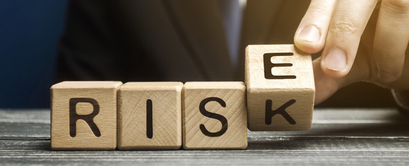 Businessman changes wooden blocks with the words Risk and Rise. Business risk management and growth performance. Risks assessment. Planning strategies and achieving goals.