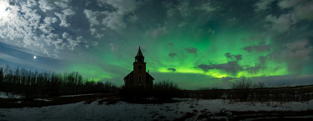 Silhouette of dilapidated church in small Canadian prairie locations with Northern Lights and stars in the night sky.