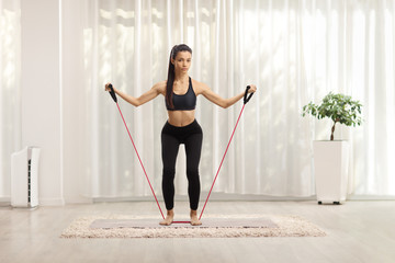 Full length portrait of a slim young female exercising with a stretching band Fotomurales