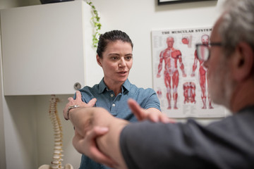 Natural medicine practitioner assessing client