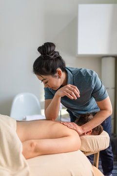 Masseuse treating client in treatment room