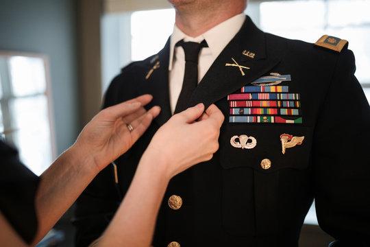 Close up wife helping husband put on military dress uniform