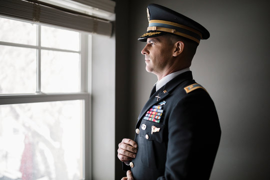 Male soldier in military dress uniform standing at window