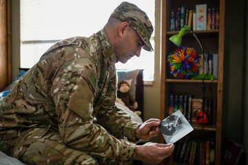 Male soldier reminiscing over childhood photographs in bedroom