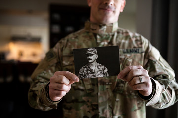 Portrait male soldier holding photograph of military ancestor