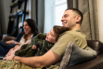 Happy military family relaxing and watching TV on sofa