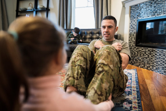Daughter helping soldier father with push ups in living room
