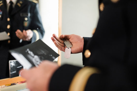 Close up male military officer looking at old dog tags and photograph