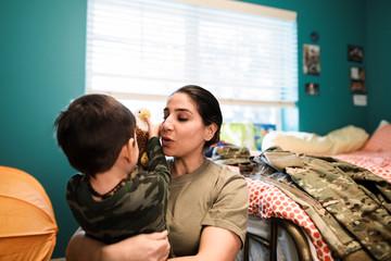 Affectionate soldier mother hugging son in bedroom