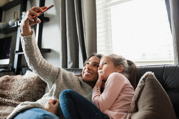 Mother and daughter taking selfie with camera phone on sofa