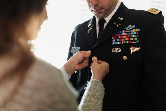 Wife helping husband button military dress uniform