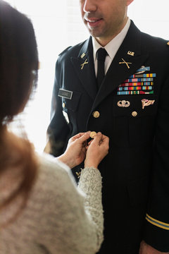 Wife helping husband with military dress uniform
