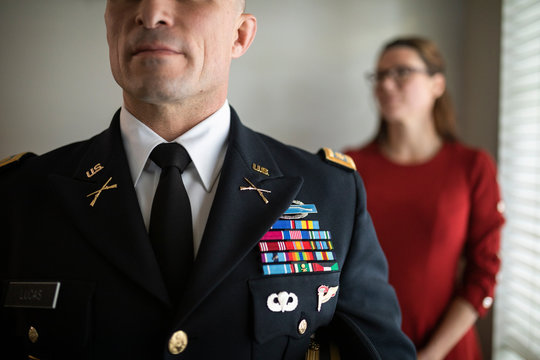 Close up wife standing behind military officer in dress uniform