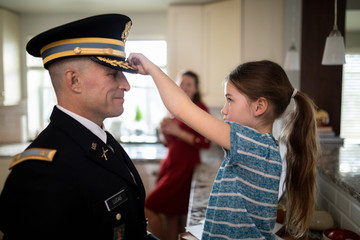Daughter adjusting dress uniform hat of military father in kitchen