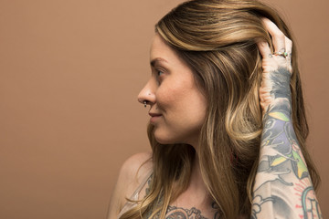 Profile portrait of confident woman with tattoos and nose ring