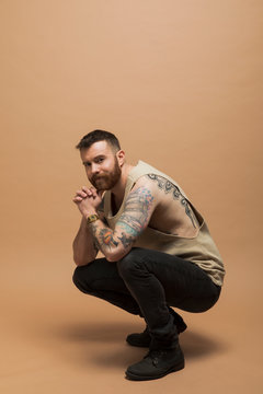 Portrait of confident transgender man with beard and tattoos
