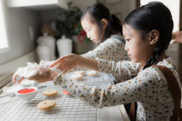 Sisters putting jam on biscuits in kitchen