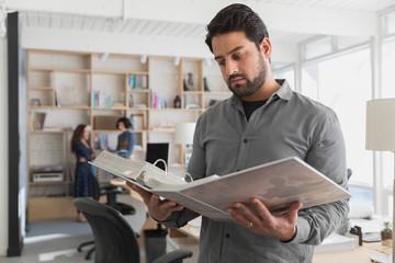 Designer looking at folder in creative studio