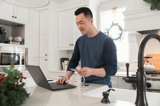 Man online shopping for Christmas with credit card using laptop