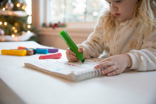 Girl drawing with color pens with Christmas tree in background