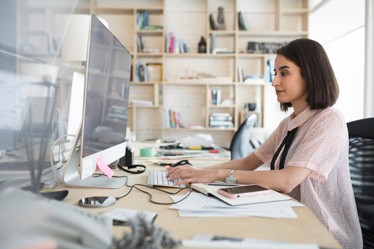 Businesswoman using computer in creative office