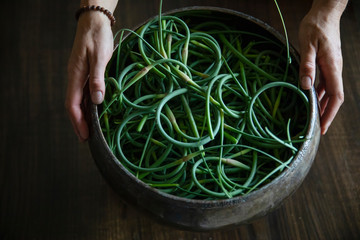 Curled green garlic scapes in rustic bowl