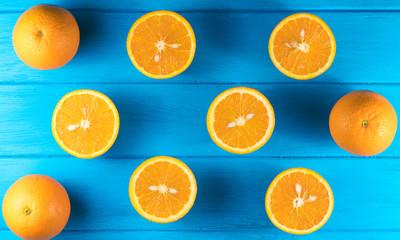 Foto op Canvas Vruchten cut oranges on a blue wooden background