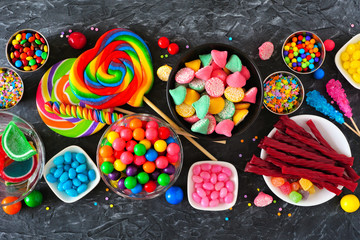 Colorful sweet candy buffet table scene. Above view over a dark stone background.