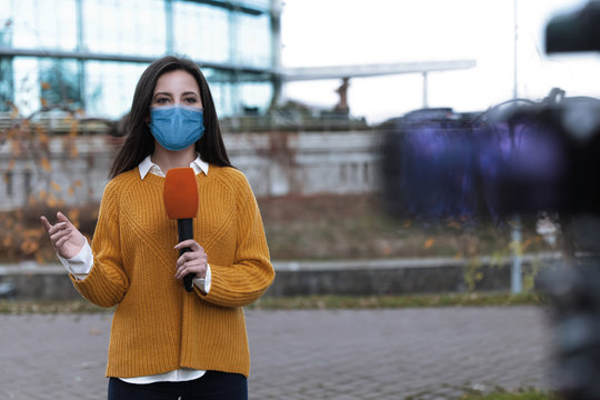 Young journalist with medical mask and microphone working on city street. Virus protection