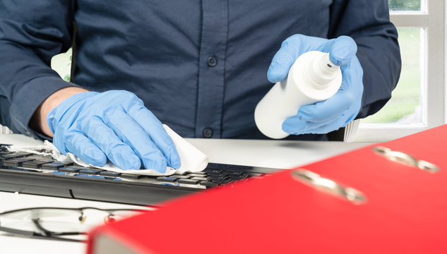 person cleans the office keyboard with a disinfectant