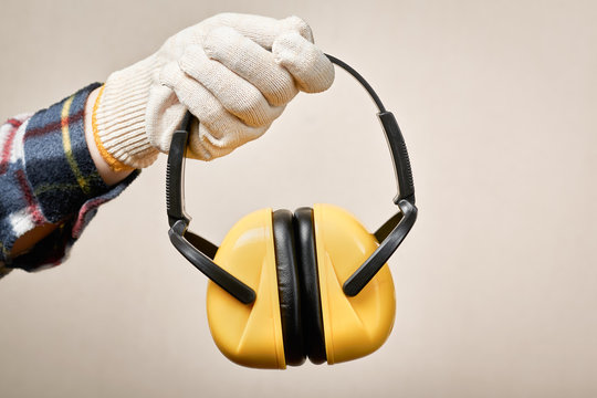 Worker's hand giving protective earphones: hearing protection and labor protection concept