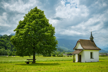 Wall Mural - Bench under the tree close to small chapel near Wichelsee close to Sarnen in Switzerland